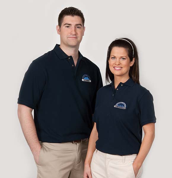Man & Woman wearing logo'd polo uniforms