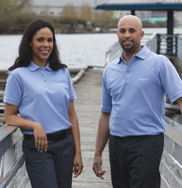 Two staff members standing at marina with logo polos